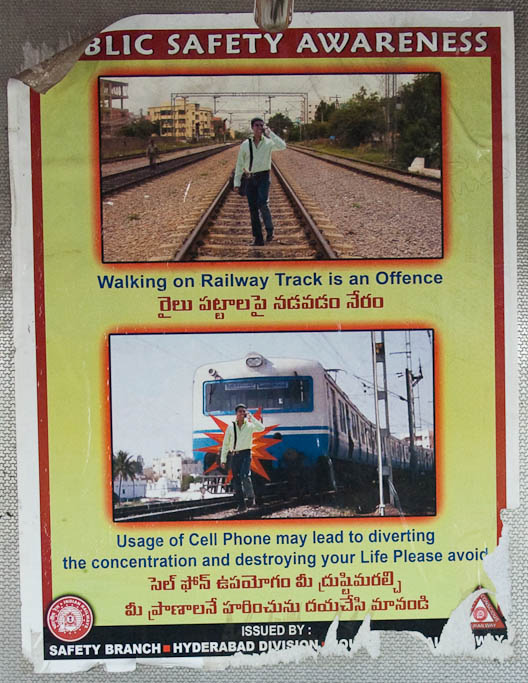 "A sign warns in English and Telugu, ""Walking on Railway Track is an Offence...Usage of Cell Phone may lead to diverting the concentration and destroying your Life Please avoid"". The accompanying photos show a person both walking on the tracks and talking on a phone, getting him hit by a train in the second photo."