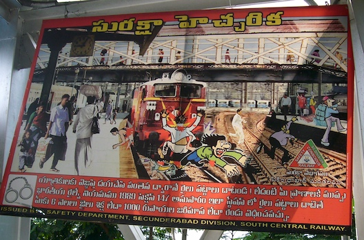 A railway safety sign at Hyderabad's Lingampally MMTS station exhorts passengers in Telugu to use the footbridge rather than cross on the tracks.